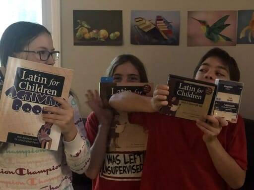 Three kids with Latin for Children activity book, workbook, DVD video instuction, audio chants, and card game.