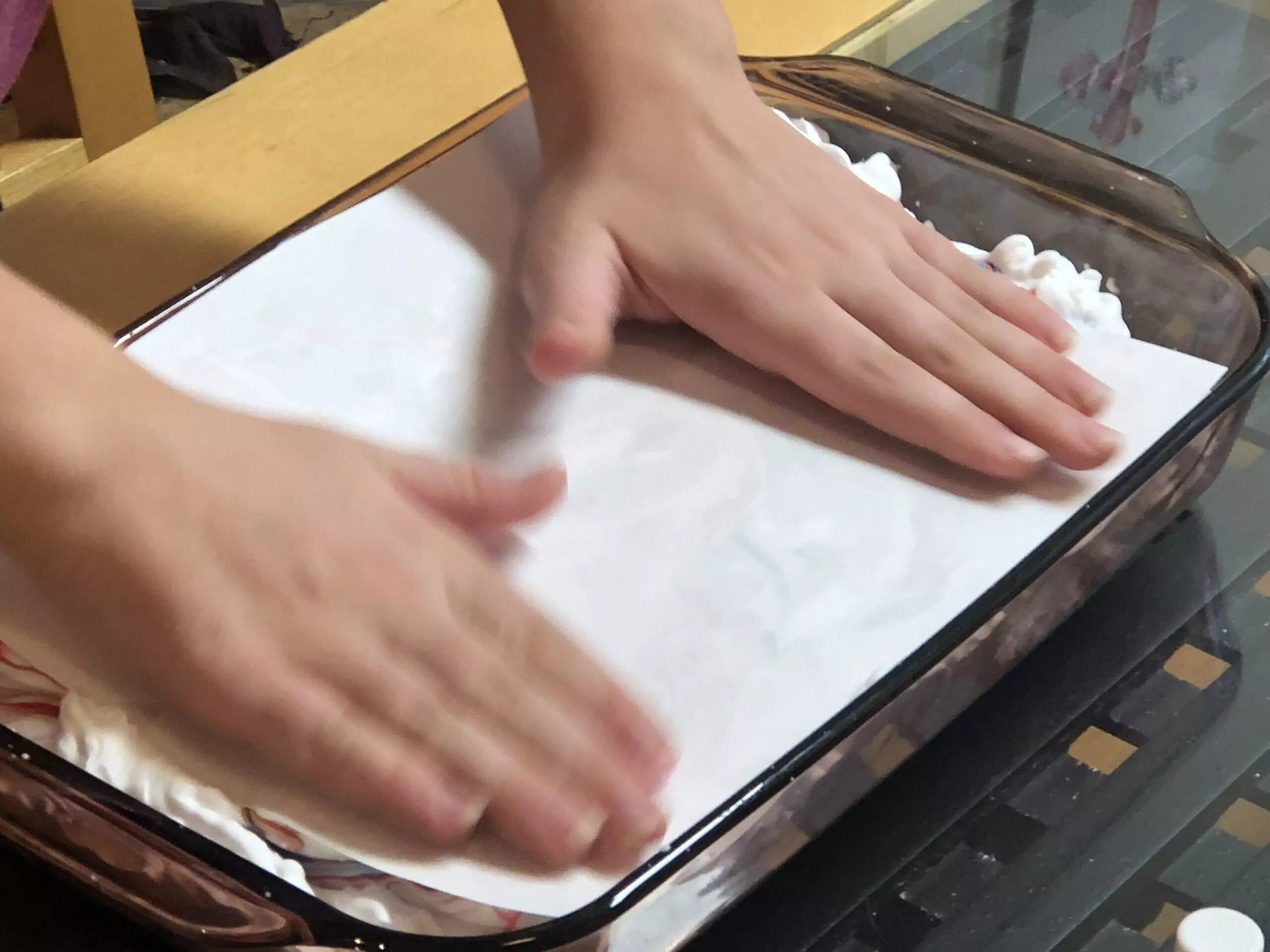 With the decorated side of the paper facing down, press gently on the shaving cream.