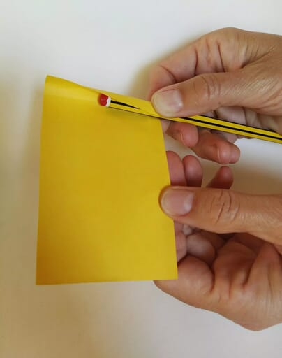 Wrap yellow construction paper around pencil.